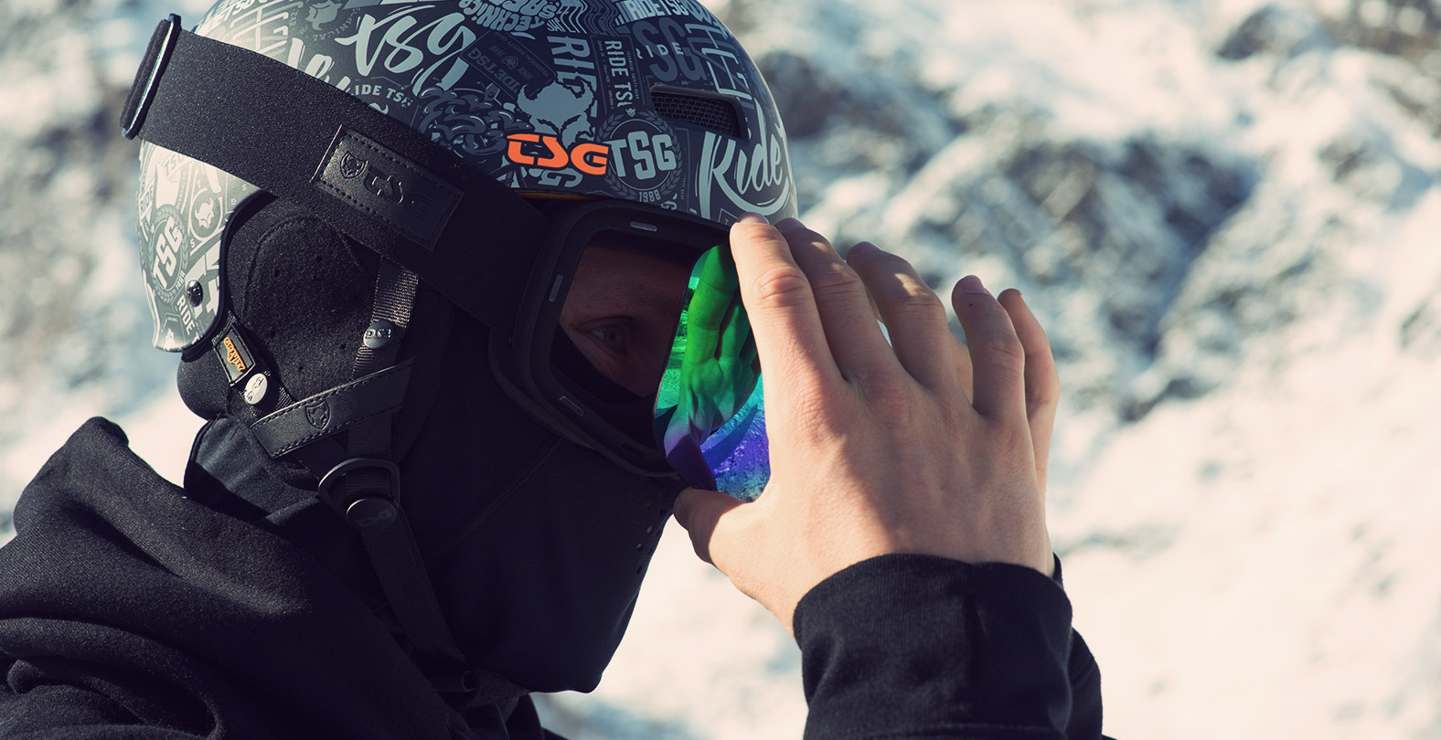 snowboarder changing magnetic lens of TSG Goggle Three