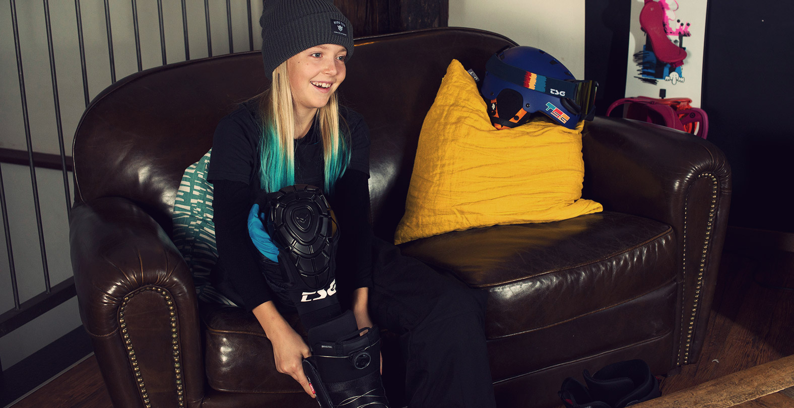 snowboard girl Kona Ettel putting on TSG knee guards