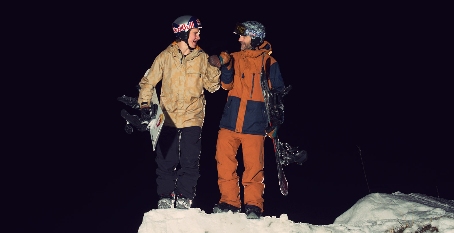 snowboarder David Hablützel and Gian Simmen cheering on the kicker during TSG night shooting in Saas Fee